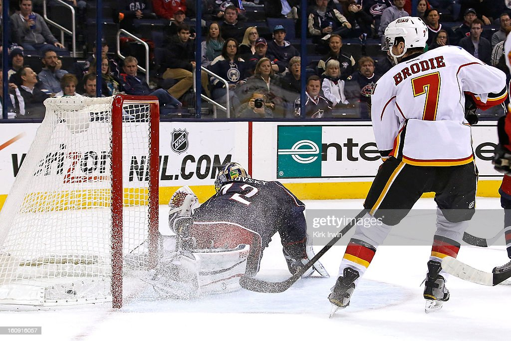 T.J. Brodie #7 of the Calgary Flames watches as <a gi-track='captionPersonalityLinkClicked' href=/galleries/search?phrase=Sergei+Bobrovsky&family=editorial&specificpeople=4488556 ng-click='$event.stopPropagation()'>Sergei Bobrovsky</a> #72 of the Columbus Blue Jackets is unable to stop the game winning shot from <a gi-track='captionPersonalityLinkClicked' href=/galleries/search?phrase=Alex+Tanguay&family=editorial&specificpeople=203231 ng-click='$event.stopPropagation()'>Alex Tanguay</a> #40 of the Calgary Flames during the overtime period on February 7, 2013 at Nationwide Arena in Columbus, Ohio. Calgary defeated Columbus 4-3 in overtime.