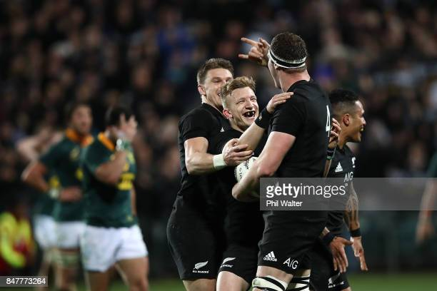 Brodie Retallick of the All Blacks celebrates his try with Beauden Barrett and Damian McKenzie during the Rugby Championship match between the New...