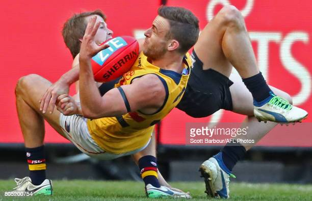 Brodie Smith of the Crows and Liam Sumner of the Blues compete for the ball during the round 15 AFL match between the Carlton Blues and the Adelaide...