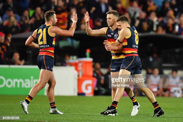 Brodie Smith of the Crows celebrates with Rory Atkins and Jake Kelly of the Crows after kicking a goal during the AFL First Qualifying Final match...