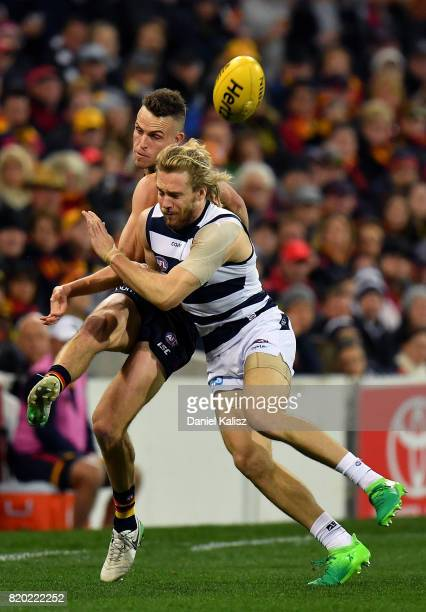Brodie Smith of the Crows gets a kick away as Cameron Guthrie of the Cats tackles during the round 18 AFL match between the Adelaide Crows and the...