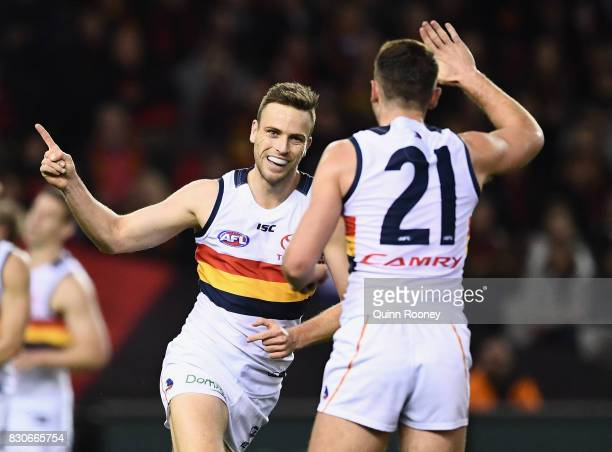 Brodie Smith of the Crows is congratulated by Rory Atkins after kicking a goal during the round 21 AFL match between the Essendon Bombers and the...