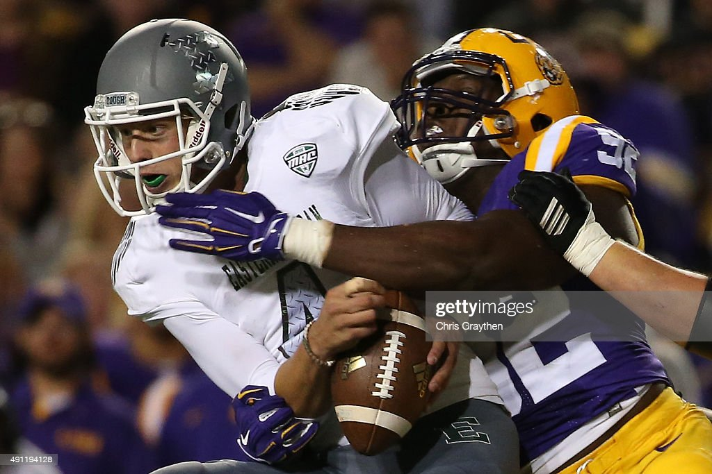 Brogan Roback of the Eastern Michigan Eagles is sacked by Lewis Neal of the LSU Tigers at Tiger Stadium on October 3 2015 in Baton Rouge Louisiana