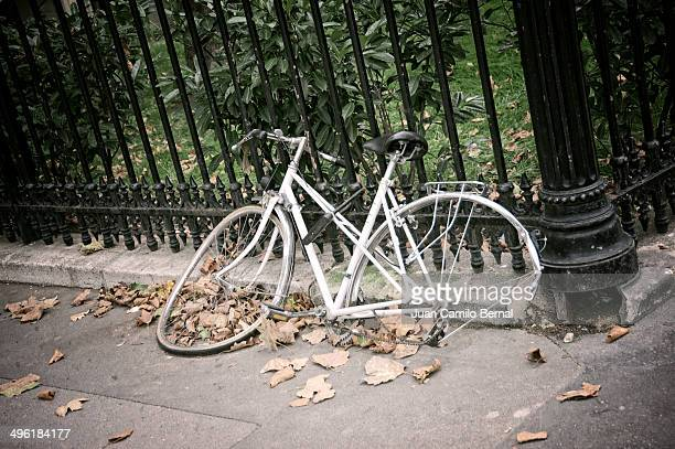 Broken bicycle against fence