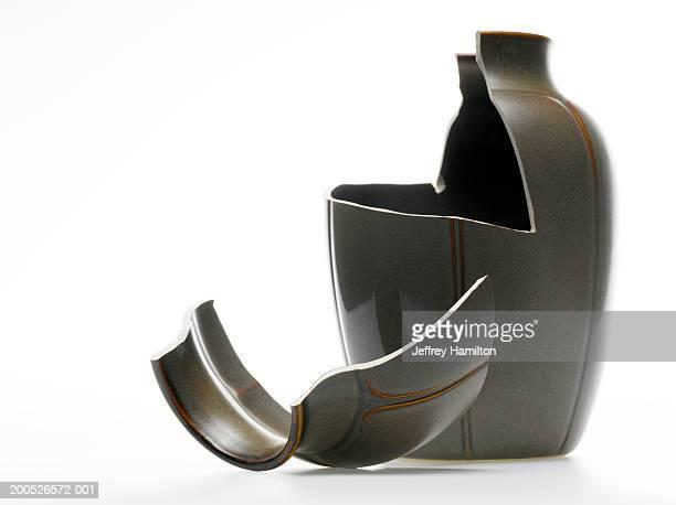 Broken black vase against white background (still life)