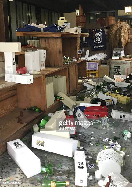 Broken bottles lie on a floor at a liquor store in Kurayoshi City Tottori Prefecture on October 21 2016 A strong 62 magnitude earthquake hit western...