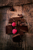 Broken chocolate bar with red ripe  raspberries on dark brown  background close up, macro