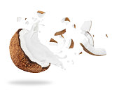 Broken coconut with milk splash, isolated on white background