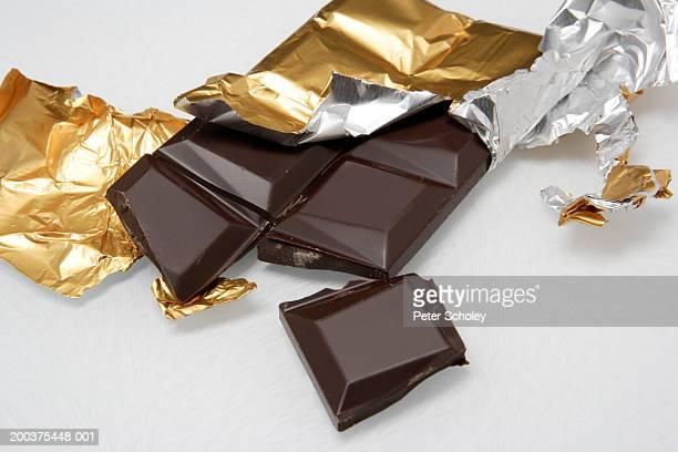 Broken dark chocolate bar in foil, close-up