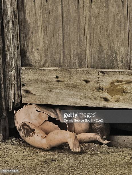 Broken Doll Under Wooden Door