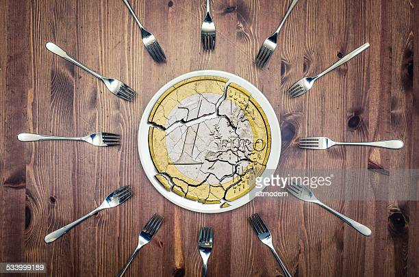 broken euro coin on a plate, with many forks around