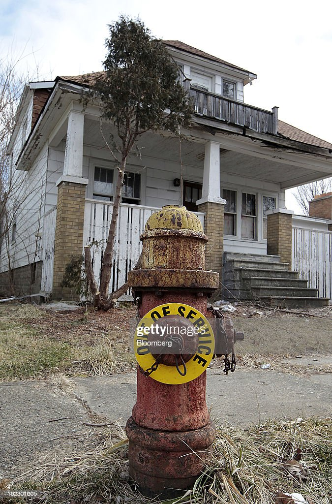 A broken fire hydrant stands in front of a dilapidated house on Mackay Street in Detroit, Michigan, U.S., on Thursday, Feb. 21, 2013. A fiscal emergency grips Detroit, according to a report ordered by Governor Rick Snyder, that opens a path to a state takeover of General Motors Co.'s home town, citing deficits that have stymied city officials after a $326.6 million gap last year. Photographer: Jeff Kowalsky/Bloomberg via Getty Images