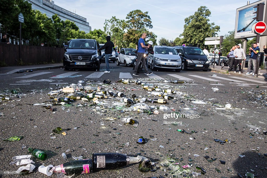 Broken glass bottles and debris litter a road as French cab drivers protest against Uber Technologies Inc.'s car sharing service in Paris, France, on Thursday, June 25, 2015. French taxi drivers are on indefinite nationwide strike as they demand a government crackdown on what they say is Uber's use of unlicensed chauffeurs for its UberPop service. Photographer Balint Porneczi/Bloomberg via Getty Images