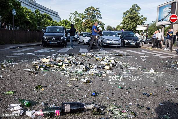 Broken glass bottles and debris litter a road as French cab drivers protest against Uber Technologies Inc's car sharing service in Paris France on...