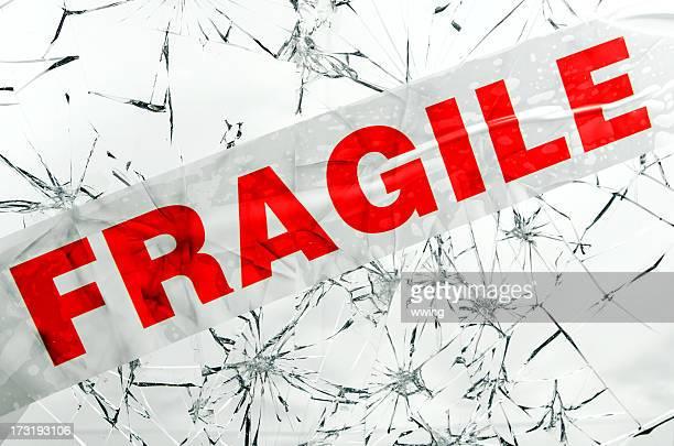 Quebrado vidro com um pedaço de fita rotulado'Fragile'sobre ela.
