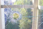 broken glass window reflecting blue sky. close up
