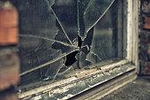 broken glass window reflecting clounding sky