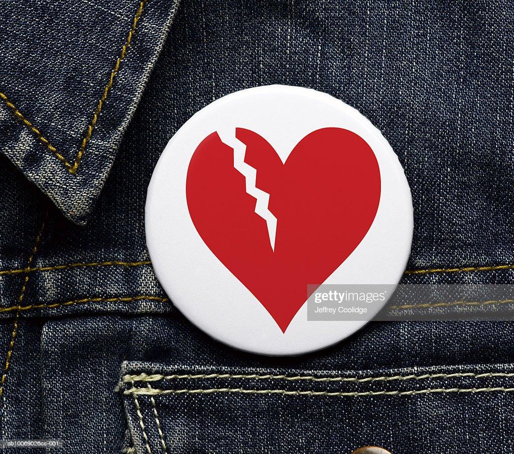 Broken heart button on denim jacket, close-up : Stock Photo