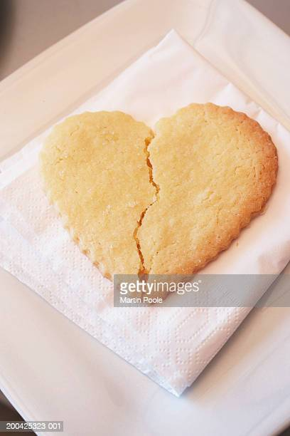 Broken heart shaped biscuit on napkin, close-up