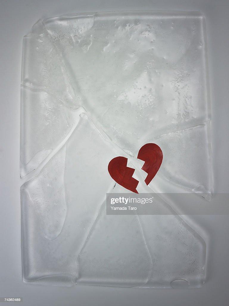 Broken heart shaped object on cracked block of ice : Stock Photo