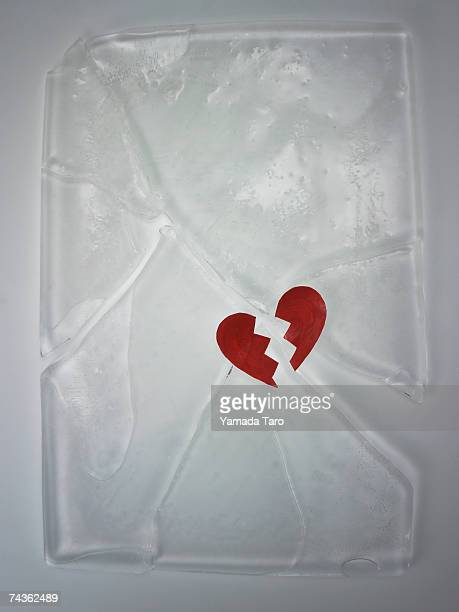 Broken heart shaped object on cracked block of ice