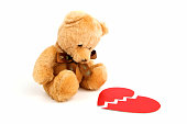 Broken heart teddy bear with Red paper heart isolated on white background. Hurts love and lonely sad doll. Front view. Close up.