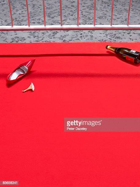 Broken high heeled shoe on red carpet