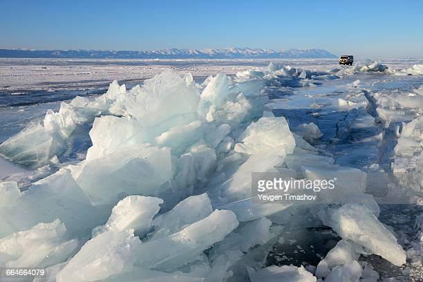 Broken ice and off road tourist vehicle, Baikal Lake, Olkhon Island, Siberia, Russia