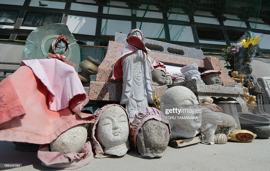 Broken images of Buddha are placed beside the ruined main building of the tsunami-hit Tozenji temple at Yuriage district in Natori, Miyagi Prefecture, on March 10, 2013, one day before the second anniversary of the March 11 earthquake and tsunami disaster. Japan will commemorate the second anniversary of a 9.0 magnitude offshore earthquake and giant tsunami that killed 15,880 people and left 2,694 unaccounted for, mainly in the Pacific coastline of the tohoku region in the nation's northeast. AFP PHOTO/Toru YAMANAKA
