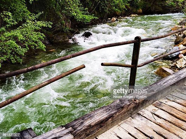 Broken Metal Railing Rod On Wooden Footbridge Over River In Forest
