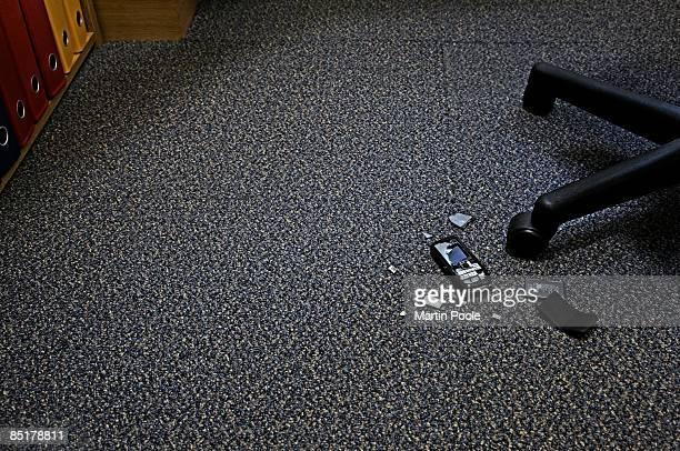 broken mobile phone on floor in office