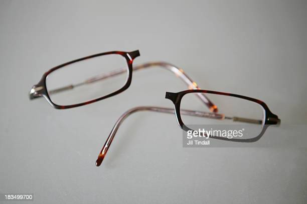 Broken pair of glasses snapped in half