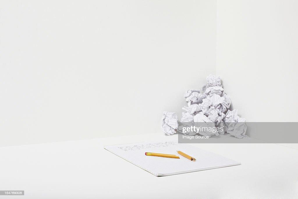 Broken pencil, notebook and crumpled paper