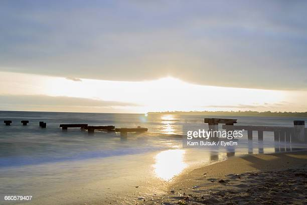Broken Pier In Sea Against Cloudy Sky At Morning