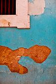 Broken plaster on blue wall
