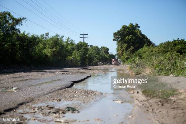 PortauPrince Haiti December 09 2012 A broken road with many potholes all over it near PortauPrince a van with people on the load area trying to pass...