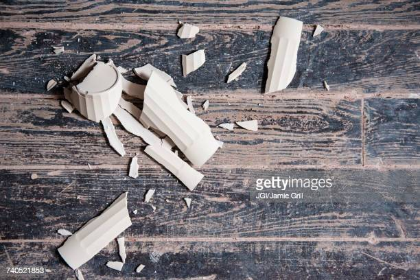 Broken shards of cup on wooden floor