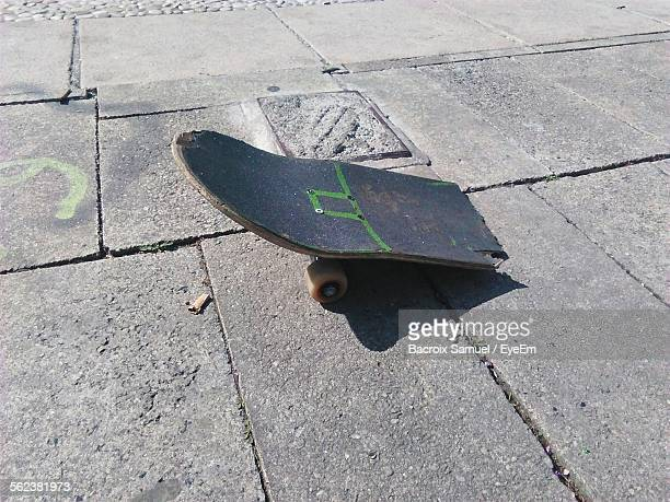 Broken Skateboard On Sidewalk