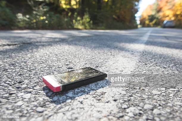Broken smartphone lying on the road