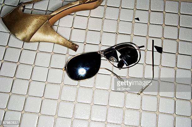 Broken sunglasses and high heel shoe