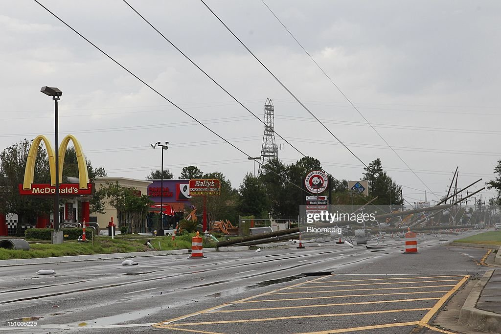 Broken telephone poles lie on the highway next to a McDonald's Corp, Rally's Hamburgers Inc. and Panda Express Inc. restaurants which remained closed due to Hurricane Isaac in Gretna, Louisiana, U.S., on Thursday, Aug. 30, 2012. Heavy rain and flooding spread inland from Tropical Storm Isaac as rising water forced evacuations in coastal areas of southeast Louisiana. Photographer: Derick E. Hingle/Bloomberg via Getty Images