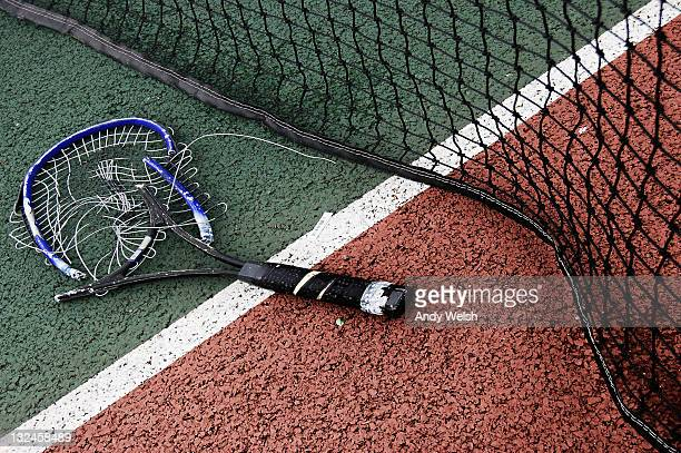 Broken tennis racket on court