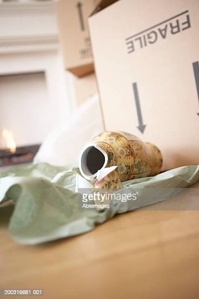 Broken vase lying on floor by box