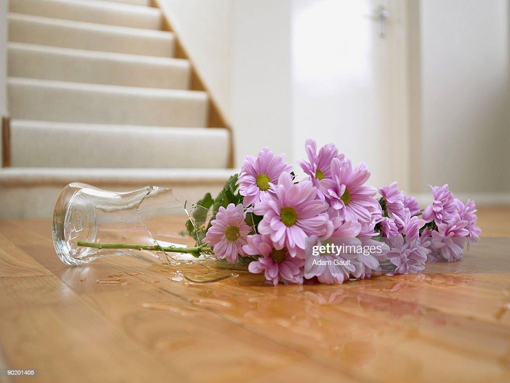 Broken vase of flowers on floor : Stock Photo