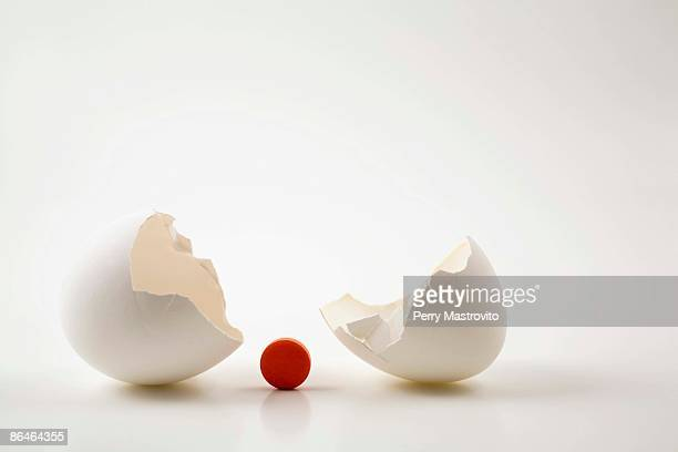 Broken white eggshell and orange medical pill