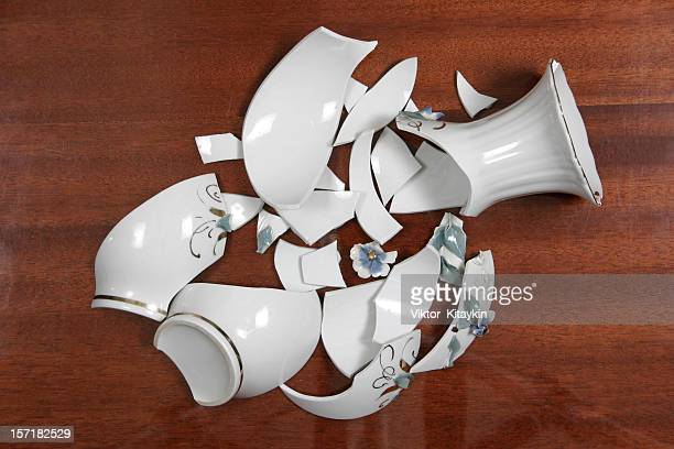 Broken white porcelain vase on wooden floor