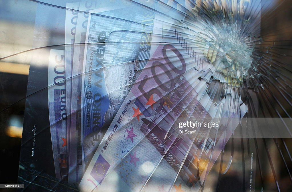 A broken window in front of a poster featuring Euro banknotes in a money transfer shop in Omonia on June 12 2012 in Athens Greece The Greek...