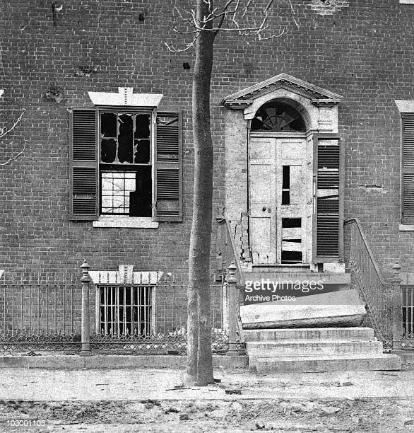 Broken windows and a damaged doorway with broken steps at Dunlop House on Bollingbrook Street showing the effects of shot and shell on the north side...