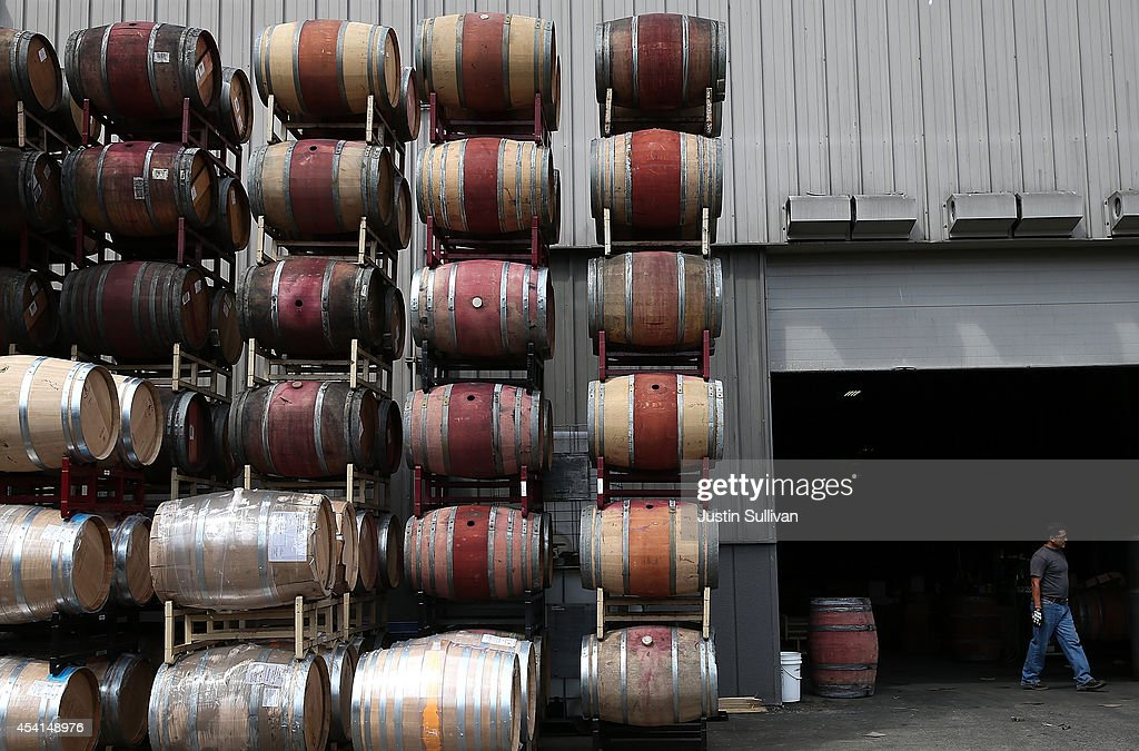 Broken wine barrels are seen stacked in a parking lot after a massive collapse at a wine barrel storage facility on August 25, 2014 in Napa, California. A day after a 6.0 earthquake rocked the Napa Valley, residents and wineries are continuing clean up operations.