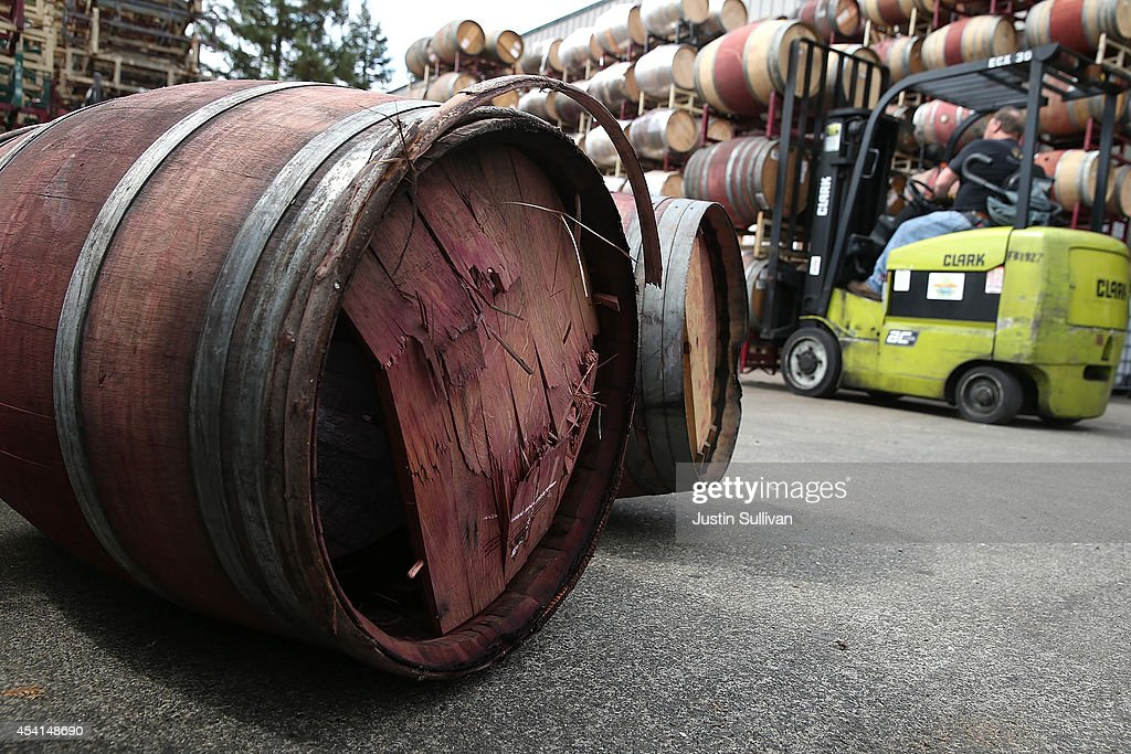 Broken wine barrels sit in a parking lot after a massive collapse at a wine barrel storage facility on August 25, 2014 in Napa, California. A day after a 6.0 earthquake rocked the Napa Valley, residents and wineries are continuing clean up operations.
